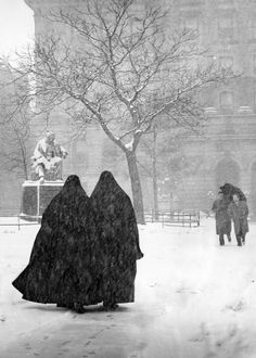 A beautiful black and white photo by Irving Stein of two nuns walking together as it snows in New York City, circa 1946.