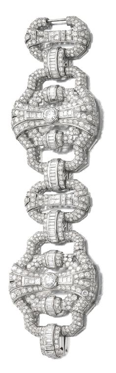 DIAMOND BRACELET, 1930S Designed as a wide, articulated band of open work plaques set with circular- and single-cut diamonds, length approximately 195mm, French assay mark, two small diamonds deficient.