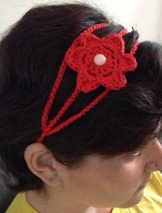Faixa para cabelos com flor de crochê.