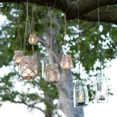 lanternes DIY en bocaux à confiture accrochées aux branches d'un arbre dans le jardin