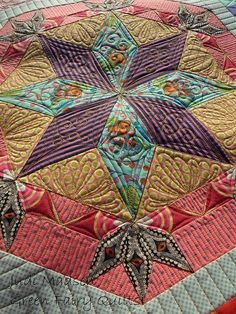 Green Fairy Quilts - Judi Madsen. Eight pointed star quilted with stripes and feathers