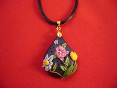 This is a one of a kind OOAK polymer clay pendant. The background is made of dark blue clay with flowers and leaves made with embroidery