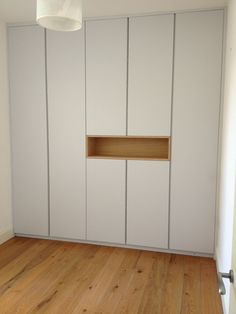 Three metre tall wardrobe. Spray painted doors with routed finger pull handles. We made an oak veneered MDF display box, to break up the large doors.
