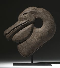 MAYA STONE HACHA OF A PELICAN HEAD, LATE CLASSIC, CA. A.D. 550-950 with elegantly curving openwork neck, long beak, deeply set eyes and scrolling featherwork along the top of the head.
