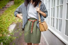 Olive green skirt, white tee, grey cardigan, brown leather belt, mustard yellow purse.