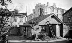 Helsinki, 1908. Vanha nainen seisoo vaatimattoman kotinsa ovella Albertinkadun ja Merimiehenkadun kulmatontilla.