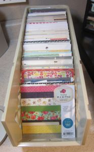 Storage solution for paper pads and their scraps. Find container of your choice in which to stand pads up, and tape an envelope to the back of each pads for scraps. Stamp-n-Storage wafer die storage boxes are one option.