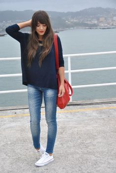 white low tops, medium rinse denim (floral?), navy sweater, red lipstick, red bag, necklace