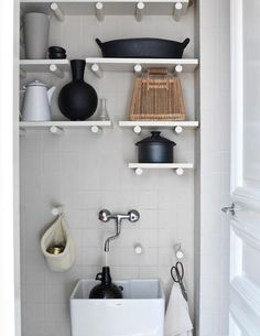 Something about the white peg-like shelving really gives this utility room a boost.