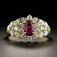 A bright rich, crystalline red, faceted oval ruby, weighing three-quarter carat (.74 ct. exactly), of Mozambique origin, glistens and glows from within a halo composed of bright-white round brilliant-cut diamonds, and between sprays composed of marquise and round diamonds in this delightful estate sparkler rendered in 18K yellow gold. .89 carats total diamond weight. A cheerful right hand ring or non-conformist engagement ring. Currently ring size 6 1/4.