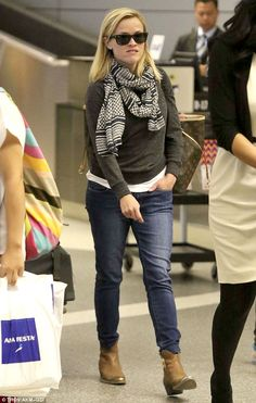 Travelling  Reese was casually hip in jeans, grey sweater, scarf and cowgirl boots