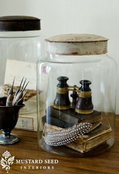 Display feathers, vintage books, and antique binoculars in a glass jar. | missmustardseed.com