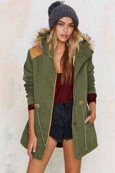 The Dakota Anorak is army green and features faux fur trim, hoodie, and drawstring waistline.