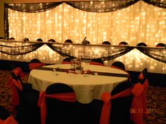 Head table: White drapery/lights backdrop, black draping, black chair covers, red chair sashes
