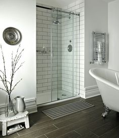 Turn an awkward alcove in a bathroom into a walk-in shower. Pictured here is Fired Earth's Lotus Flower sliding door, which can be made bespoke to fit your space. Retro-style wall tiles finished with grey grout create a smart utilitarian look. Sliding Bathroom Doors, Sliding Door Design, Sliding Glass Door, Shower Doors, Sliding Doors, Barn Doors, Shower Alcove, Wood Doors, Entry Doors