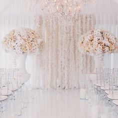 Add texture to an all-white #wedding with a feather curtain for an extra element of visual interest and dimension. Not to mention, the muted pastel #floral arrangements with feather accents are a beautiful bonus to this #ceremony space! Instagram repost