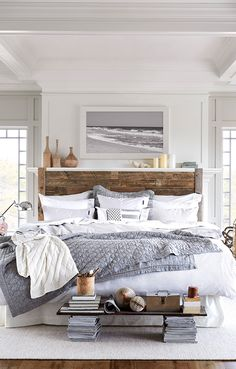 Rustic neutral coastal bedroom with a wood blank headboard and black and white ocean photograph.