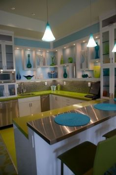 I love all the bright funky colors in this kitchen as impractical as the lac of enclosed storage is