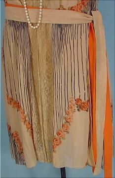 c. 1926 Deco Tea-colored and Orange Design Crepe Day Dress.Tea colored thin silk crepe fabric in two layers. The under sheath which you see in the front panel, hemmed with wide lace, and then the attached overdress, pleated from the shoulders, edged in wide ecru lace which is totally open front and back and only ties down with the separate original tie belt. The design is a print in the silk fabric. Black stripes ending in orange flowers in the deco design. Detail