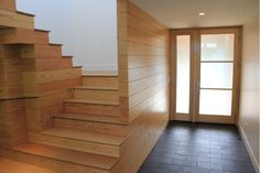 Modern staircase and entry way; wood geometric stairs, frost glass door