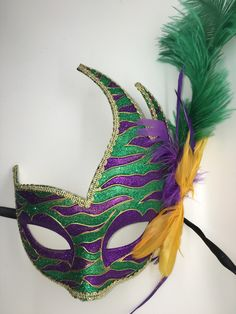 Purple and green striped mask with purple, green and yellow feathers. Ribbon ties.