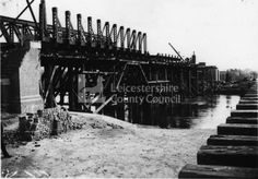 L2254 - Photographed on 3.10.1896, this is the large girder bridge that was built to take the Last Main Line across the Trent. A forest of temporary wooden frames supports the infant structure whilst the piers are constructed. Note the distinctive outline of a steam crane at work on the far end of the bridge. Logan & Hemingway was the firm responsible for building this section of the railway (Contract No.1, Annesley to Leake).   British Railways - S. W. A. Newton Collection