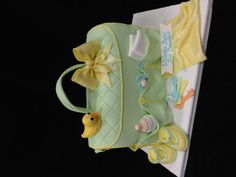 A diaper bag cake with all items made from fondant and the watchful duck...