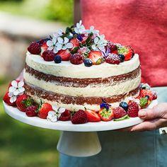 """Imponera med en lyxig """"layer cake"""" full med syrliga och söta sommarsmaker – flädermarinerade jordgubbar, lemoncurd och så överraskningen i form av vispad vit chokladpannacotta. Garnera med allsköns bär och gärna ett gäng ätbara blommor."""