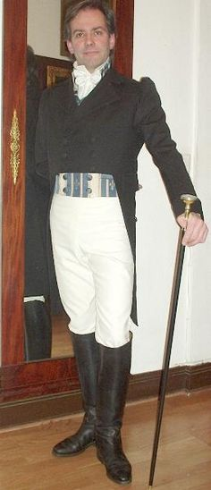 From the Regency/Empire period. Exceptionally replicated tails of black wool cloth with M-collar, closed cuffs and covered buttons. The vest is short (to the waist) with a blue and cream striped patterned fabric that also has cloth covered buttons. The shirt and cravat are made from silk taffeta.  Found at http://www.la-pompadour.de