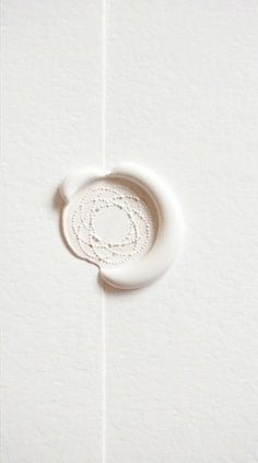 White wax seal on crisp white paper