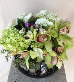 Sophistication! Sophistication! Sophistication! A glass bowl of some of nature's most exotic blooms! Including some or all of, Cymbidium Orchids, various Hydrangeas, White Snow Flower, various of Lilies, white and/ or colored Miniature Calla Lilies, and complimenting filler flowers and greenery. Did we mention... Sophistication!!!?   #laflorist #laflowers #losangelesflorist
