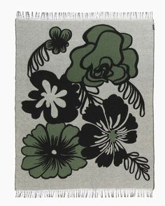 Eläköön elämä blanket by Marimekko is adorned with a lively flower pattern designed by Maija Louekari. The blanket is made of a soft and warm blend of wool, cotton and polyamide and finished with fringed ends.