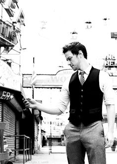 James McAvoy. Gray pants, black vest, striped tie