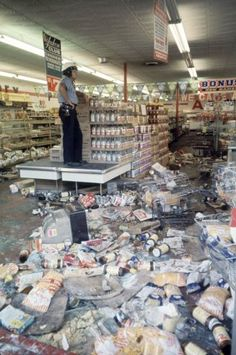 Detroit 1967: A Detroit police officer stands guard over a grocery store looted during the Riot.  Photos From the 12th Street Riot - LIFE   I remember being at the movie theater when we were told to leave because of the rioting.
