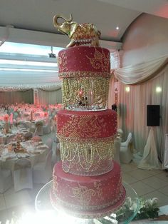 Red fondant with hand piped paisley details. Draped gold beads between each tier, with a jewelled elephant