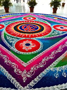 Rangoli also known as Kolam is a folk art from India. Rangoli are decorative designs made on the floors of living rooms and courtyards during Hindu festivals. They are meant to be sacred welcoming areas for the Hindu deities.