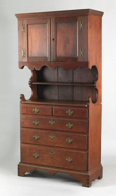 "Pook & Pook. 4/20/07. Lot 363.  Estimated: $25K - $35K.  Realized Price: $58,500.  PA. Queen Anne walnut wall cupboard, ca. 1750, the upper section with 2 paneled doors enclosing a fitted interior, over scalloped recess opening with single shelf, the base with 2 over 3 long drawers. Straight bracket feet with center drop , 79"" h., 36"" w.  Provenance: Joe Kindig, Jr. & Son Antiques. Copies of letters referring to this piece accompany the lot."