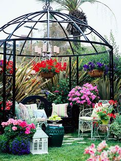 An open metal structure defines a pretty spot for relaxing. Some gazebos are for shelter, while others, such as this one, offer purely decorative elements in the landscape. An overhead candlelit fixture supplies nighttime ambiance. Hanging baskets define the open walls. When a gazebo has no sides, use plants to stand in for walls. Widely spaced pavers interspersed with grass eliminate the need for a formal floor.