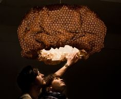 lamp is made out of hundreds of wooden triangles that she has transformed into a flexible textil.
