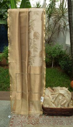 This stylish Benares net sari is coconut white and gold colored with a half and half design. One half of the sari has a beautiful lotus bhuttas woven over a coconut white base in gold zari. While t…
