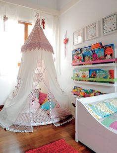 Quer coisa mais gostosa que uma cabaninha para se jogar e ler? Da Maria Florzinha, a tenda foi turbinada com tecidos da Petit retrô. Fica prático pegar os livros infantis nas prateleiras do painel ao lado, instalado junto à parede