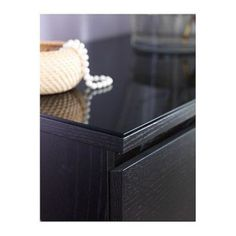 Dress up a basic Malm ikea dresser with it's matching grey-black matching glass top, add some knobs for extra flare!