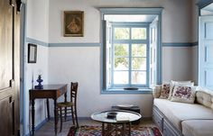The ground-floor sitting room of Forno Annex, featuring a portrait from a salon in Patmos on the wall and a cobalt blue oil lamp on the writing desk. #Greece #Interior #Design