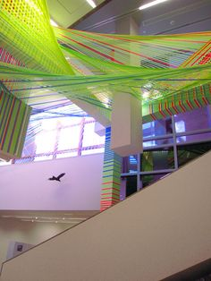 los angeles-based artist megan geckler has created a site-specific architectural installation at the wexner center for the arts in columbus, ohio. constructed from interlacing strips of vibrantly colored flagging tape,