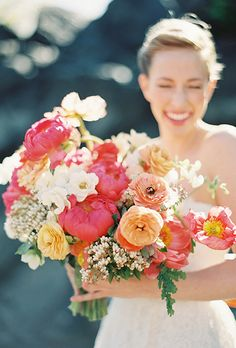 Bouquet of coral charm peonies, ranunculuses, andromedas, sweet peas, spray garden roses, and poppies | Brides.com