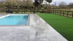 Trulawn Luxury surrounds this outdoor pool to create an attractive but durable option for a modern garden space.