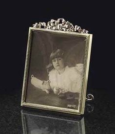 A PARCEL-GILT SILVER PHOTOGRAPH FRAME BY FABERGÉ, WORKMASTER VIKTOR AARNE, ST. PETERSBURG, 1899-1904. Rectangular, enclosing a photograph of Princess Nina Georgievna, with beaded border and surmounted by a tied-ribbon crest, the back inscribed 'Xmas 1904'. Provenance: Grand Duke George Mikhailovich and Grand Duchess Marie Georgievna; Princess Nina Georgievna Chavchavadze; Prince David Pavlovich Chavchavadze.