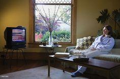 Stock Photo : Woman watching morning television wearing pajamas