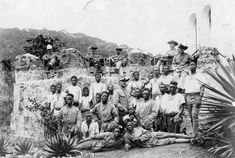 Some of the 5. Feldkompagnie based at Ebolowa. The German officers and NCOs wear 1896 Schutztruppe khaki uniforms with Südwester hats edged in red for Cameroon, one wears a white tropical helmet. Of the African soldiers some are wearing the khaki tunic with red collar edging, and some the white fatigue shirt with blue collar and three horizontal chest stripes. The red rolled fez with imperial eagle is worn by most of them. As well as the soldiers the photograph seems to include African…