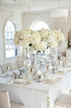 Crystals and mercury glass add the sparkle to this all-white set-up. Note the use of the trim and tassels along the edges and corners of the tables - a clever way to add shimmer to white linens. Tack onto the trestle tables with drawing pins.